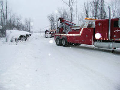 Severe winter storm recovery of a rolled over tractor and trailer